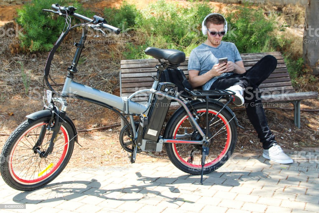 Hombre con bicicleta eléctrica sentado en el parque con auriculares - foto de stock
