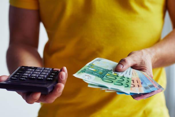 Hombre con billetes de euro y calculadora - foto de stock