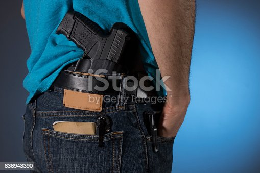 Man with a variety of everyday carry (edc) items; a gun, notes, pocket knife, and flashlight