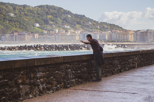 Man with extended hands and catching waves on seaside. Tourist on seacoast of San Sebastian, Spain. Freedom and happiness concept. Lonely person on seaside of Bay of Biscay in water mist.