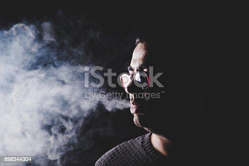 Man with eyeglasses vaping on black background