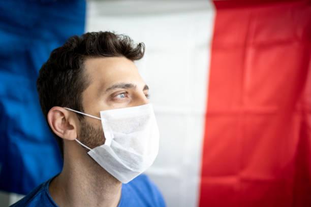 homme avec le masque de visage et le drapeau français sur le fond - france photos et images de collection