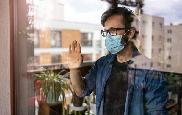 man with face mask looking out of window - trap house stock pictures, royalty-free photos & images