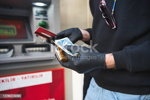 945598452 istock photo man with face mask on a bank ATM using a credit card during a coronavirus pandemic 1226023093