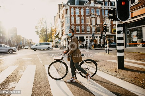 istock Man with face mask pushing bicycle in the city during coronavirus pandemic lockdown 1243563980