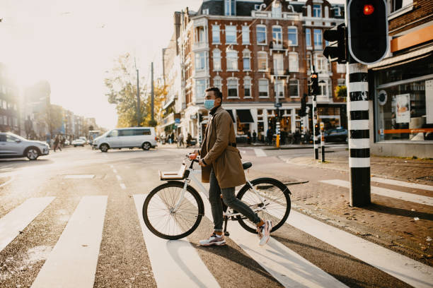 Man with face mask pushing bicycle in the city during coronavirus pandemic lockdown stock photo