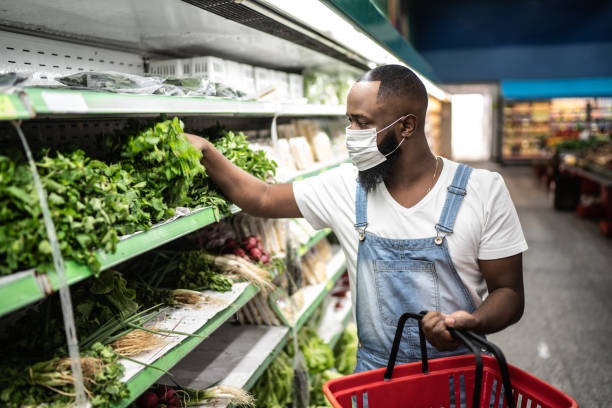 Man with face mask walking and shopping in supermarket stock photo