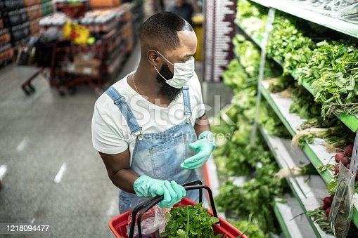 927641110 istock photo Man with face mask walking and shopping in supermarket 1218094477