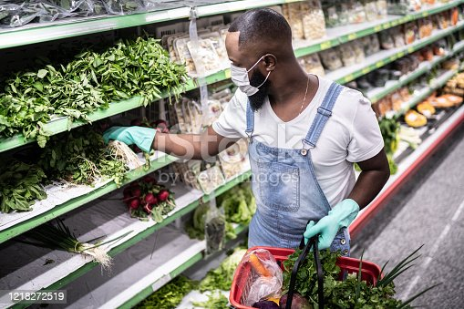 927641110 istock photo Man with face mask walking and shopping in supermarket 1218272519