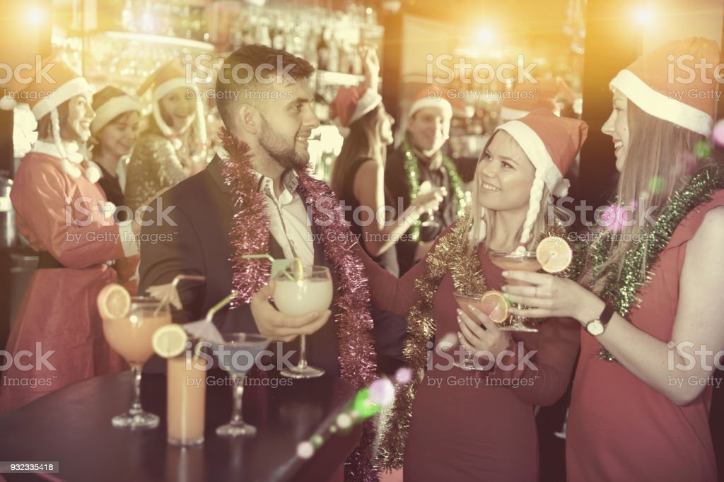 Man with females on corporate new year party in bar stock photo