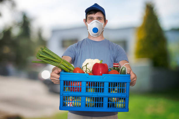 man with ffp3 respirator face mask is delivering food and groceries during virus epidemic. - essential workers stock pictures, royalty-free photos & images