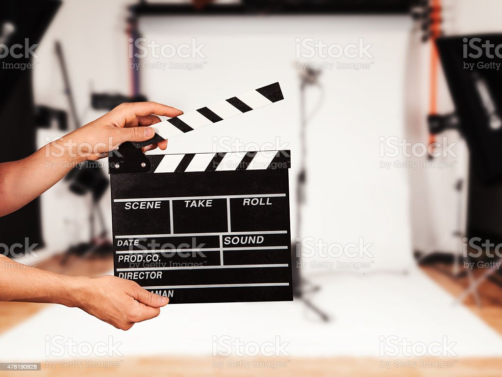 Man with film clapper in studio stock photo