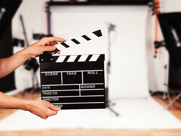 Man with film clapper in studio stock photo