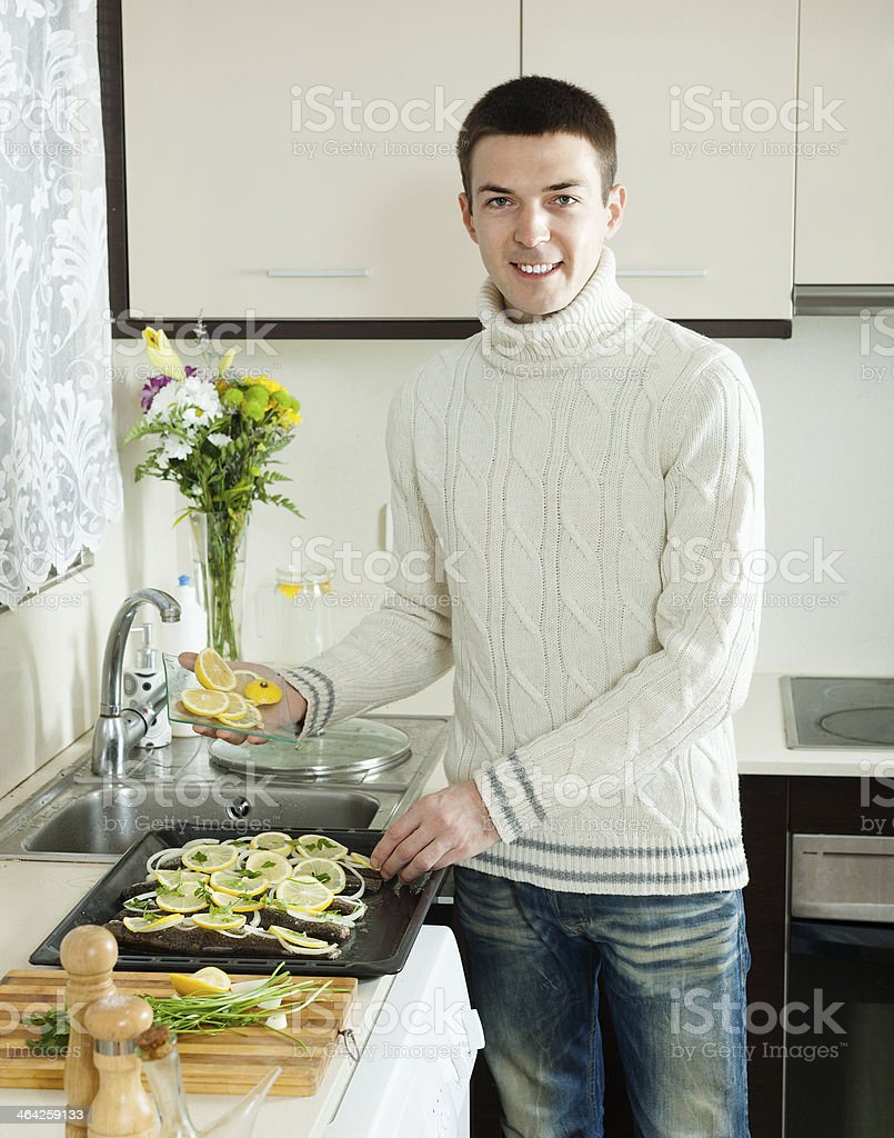 man with fish on roasting pan stock photo