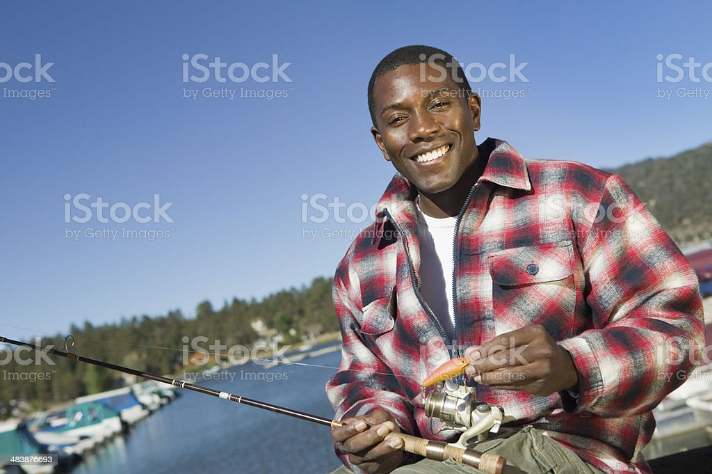 Man with Fishing Pole and Lure at Lake stock photo
