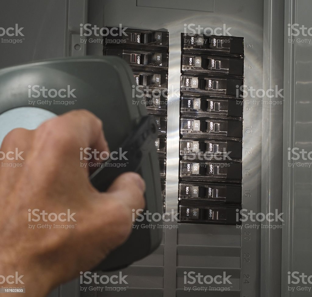 man with flashlight at residential service panel stock photo