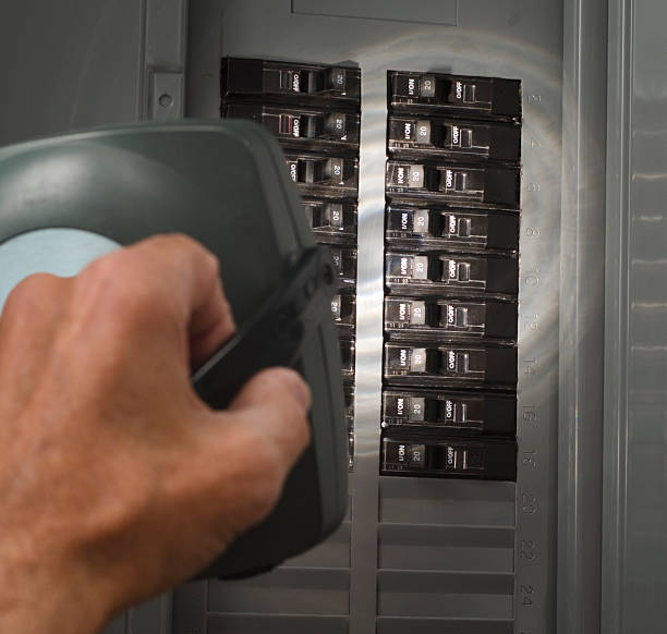 man with flashlight at residential service panel - fuse box stock photos and pictures