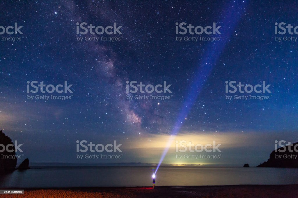 A man with flashlight looking to the night sky and Milky Way stock photo