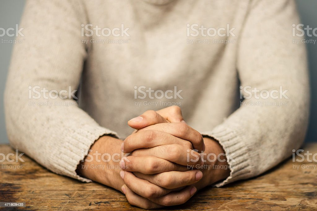 Man with folded hands seated at desk royalty-free stock photo