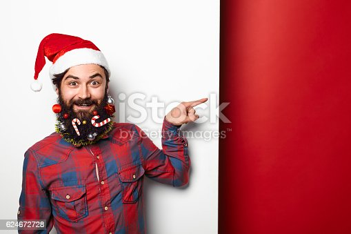 istock man with funny decorated beard pointing to the side 624672728