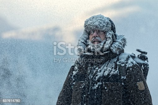 Man with  furry and coat shivering in storm with cloudy skies and snowflakes blowing in wind