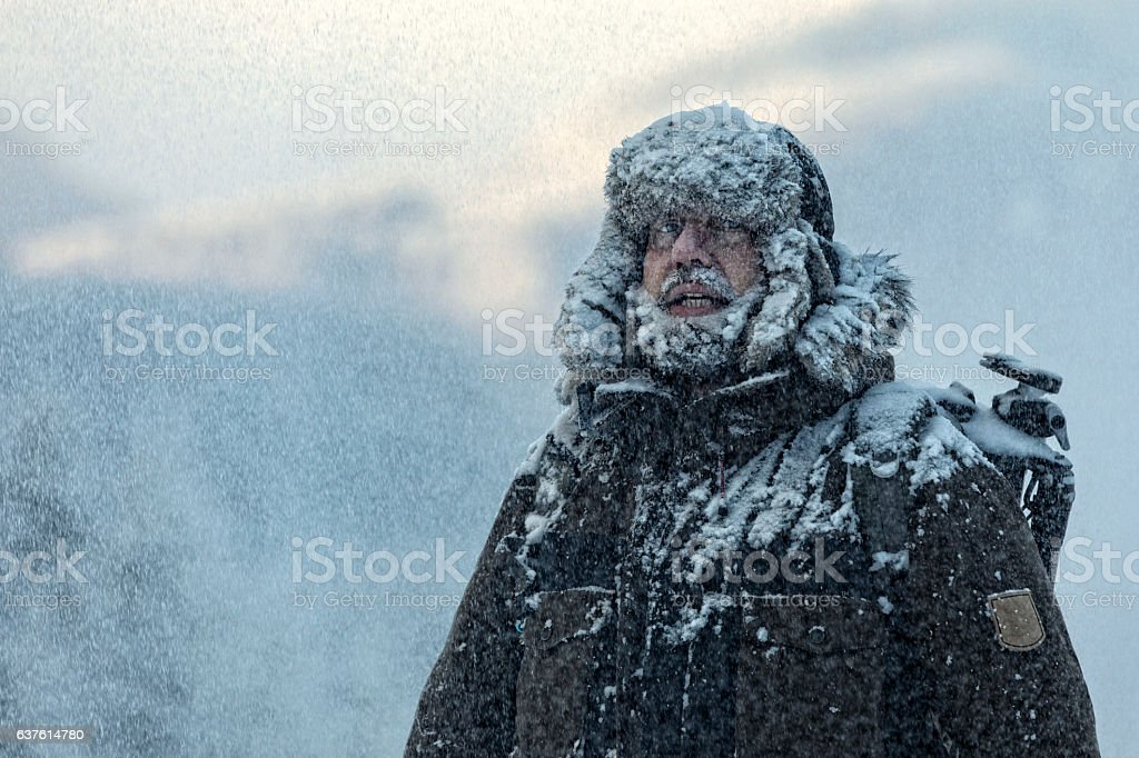 Man with furry  in snowstorm with cloudy skies and snowflakes stock photo