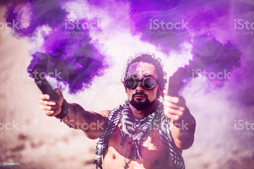 Hombre con gafas steampunk futurista y bombas de humo en el desierto - foto de stock