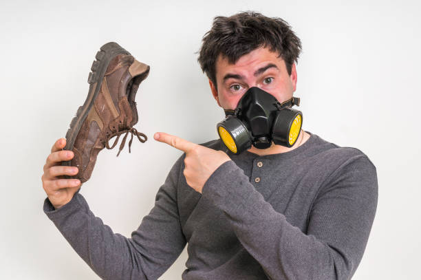 Man with gas mask is holding dirty stinky shoe stock photo