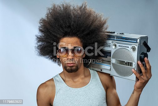 Man with big afro hair  listening to funky music on ghetto blaster, studio shot
