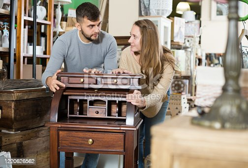 Young man with girlfriend admiring vintage wooden bureau in their apartment