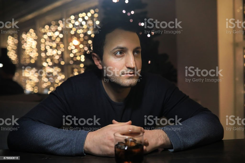 man with glass of whisky in the pub on night stock photo