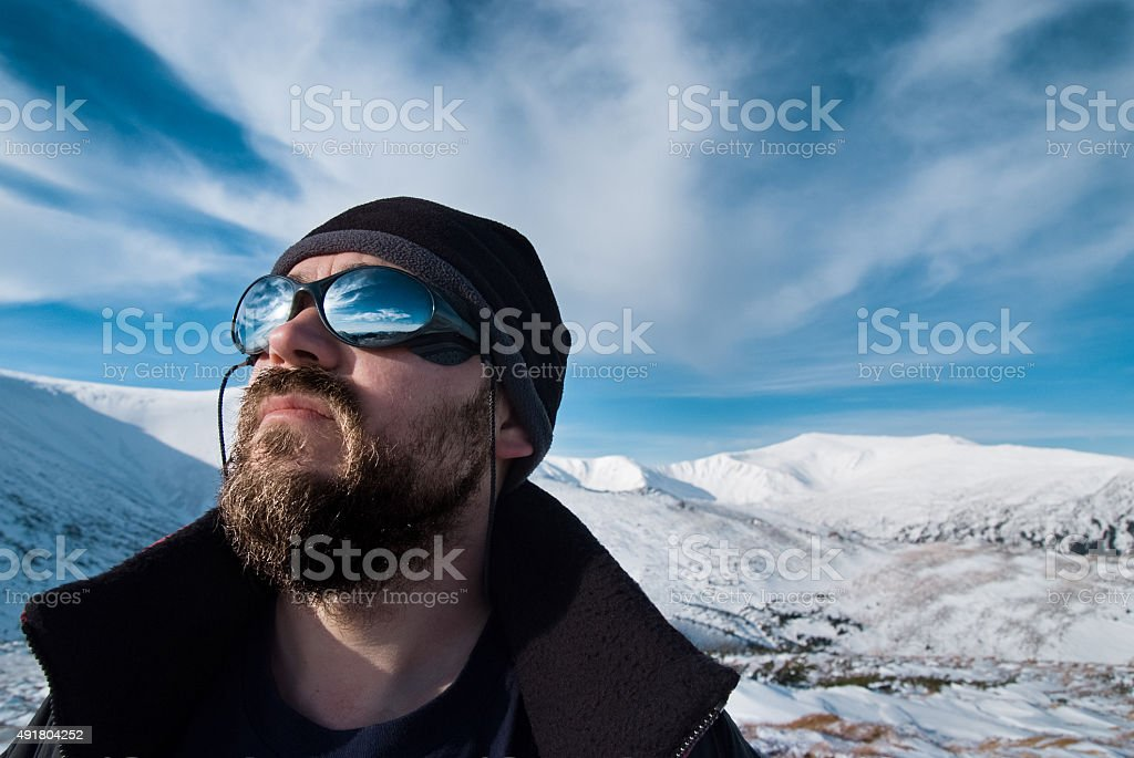 Man with glasses and a beard in the snowy mountains stock photo