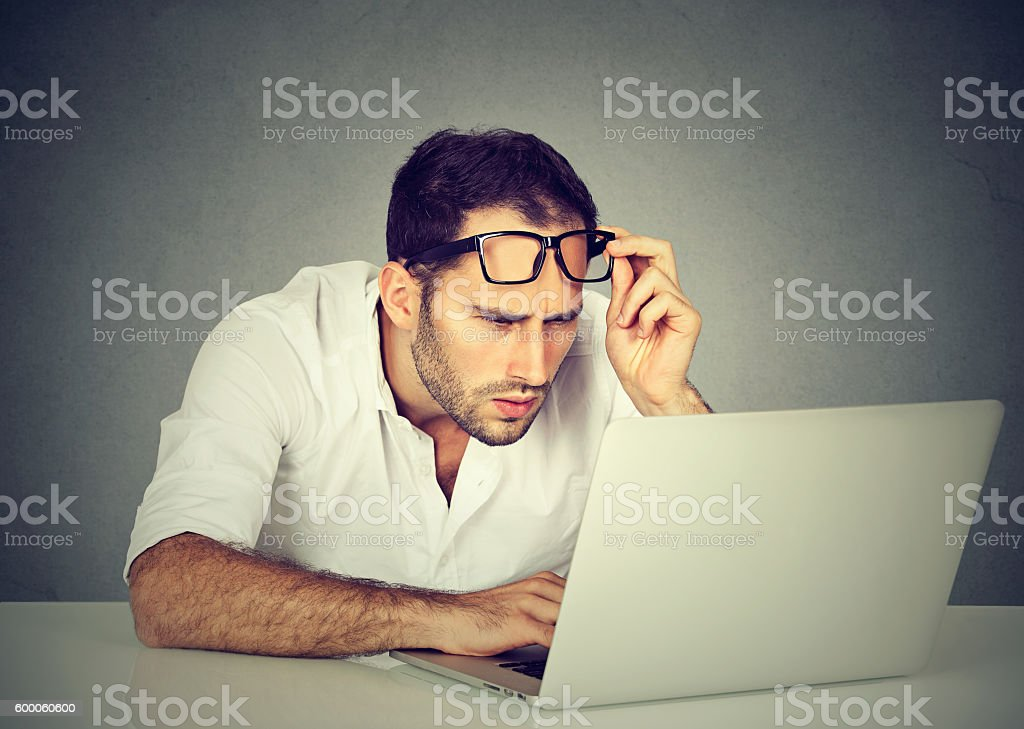 man with glasses having eyesight problems with laptop stock photo