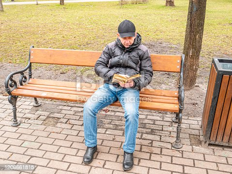 A man with glasses is reading a book on a bench. People. Winter clothes. Place for text. City life
