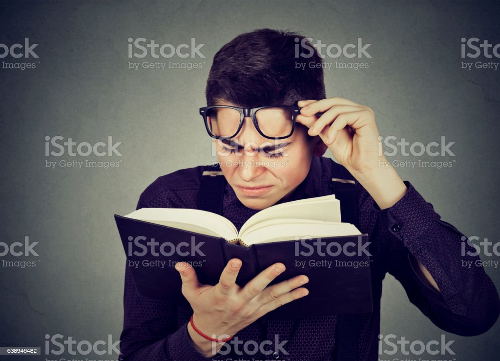 man with glasses reading book has sight problems stock photo