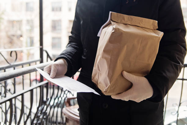 Man with gloves delivering food at the door. stock photo