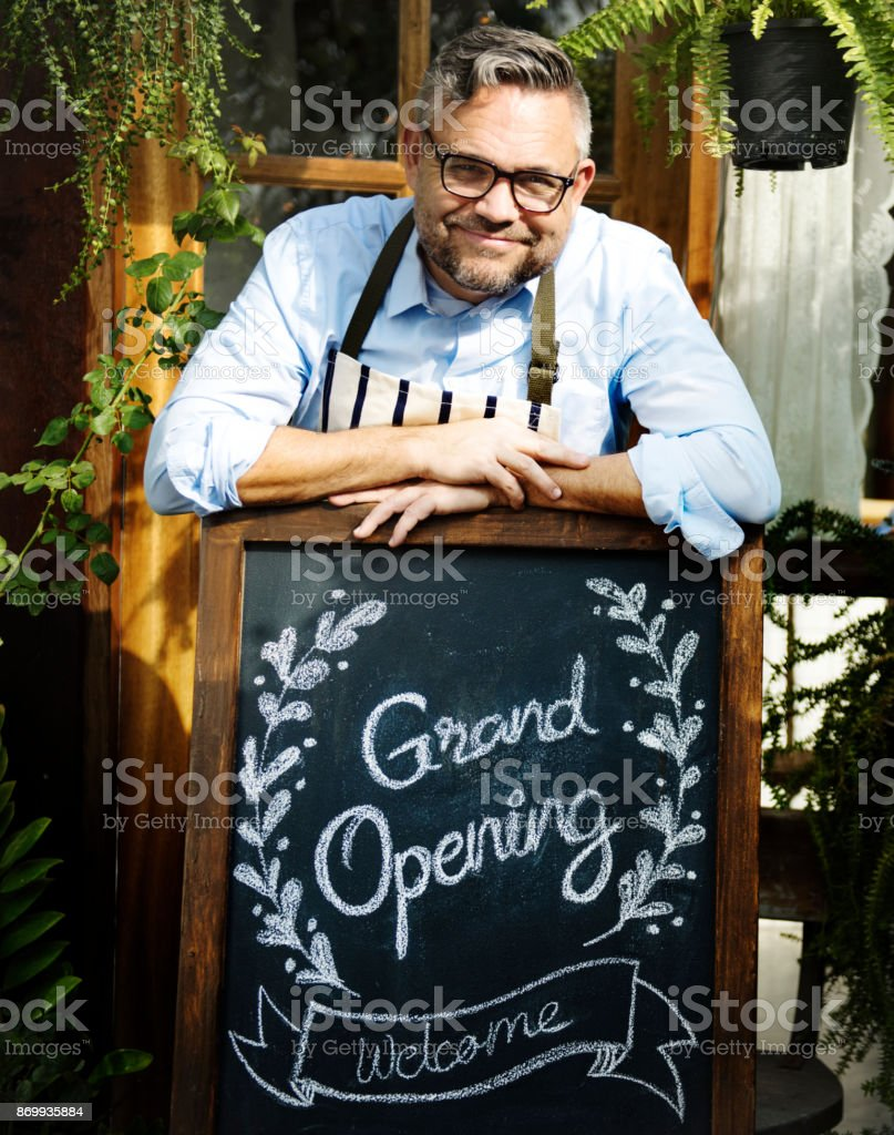Man with grand opening blackboard stock photo