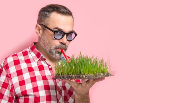 mann mit grünen detox saft konzept - mensch isst gras stock-fotos und bilder