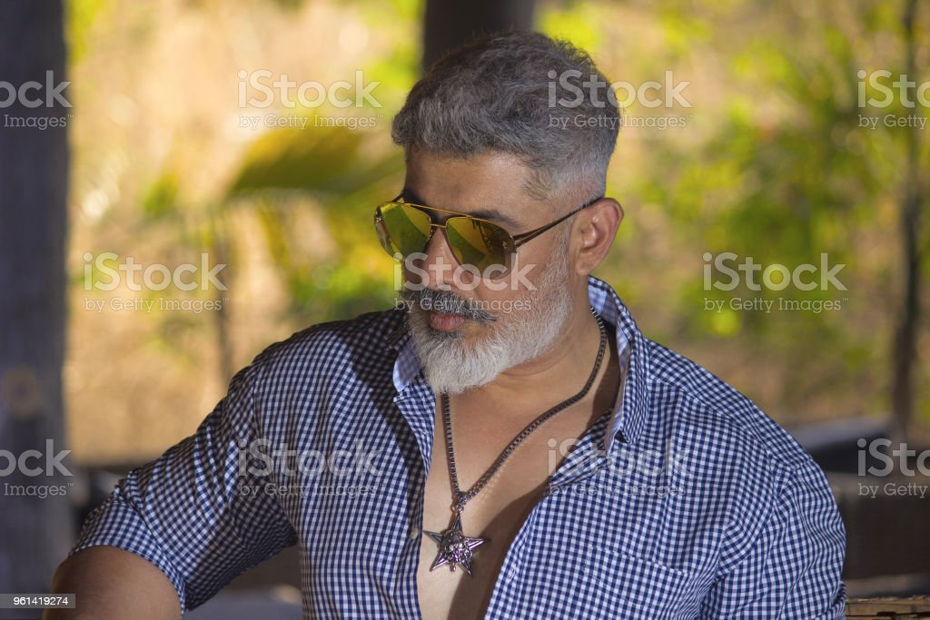 Man with grey hair grey beard in smart casuals looking at camera stock photo