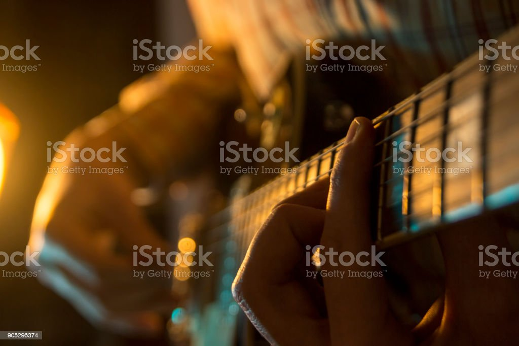 Man with guitar, male hand playing on electric guitar. Close-up. stock photo