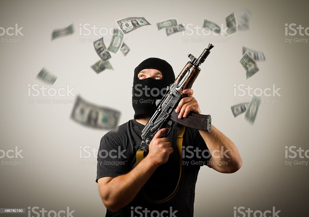 Man with gun and dollar banknotes. stock photo