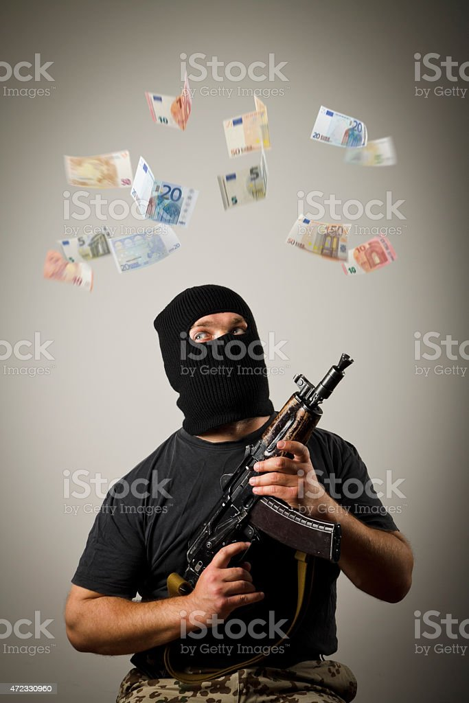Man with gun and euro banknotes. stock photo