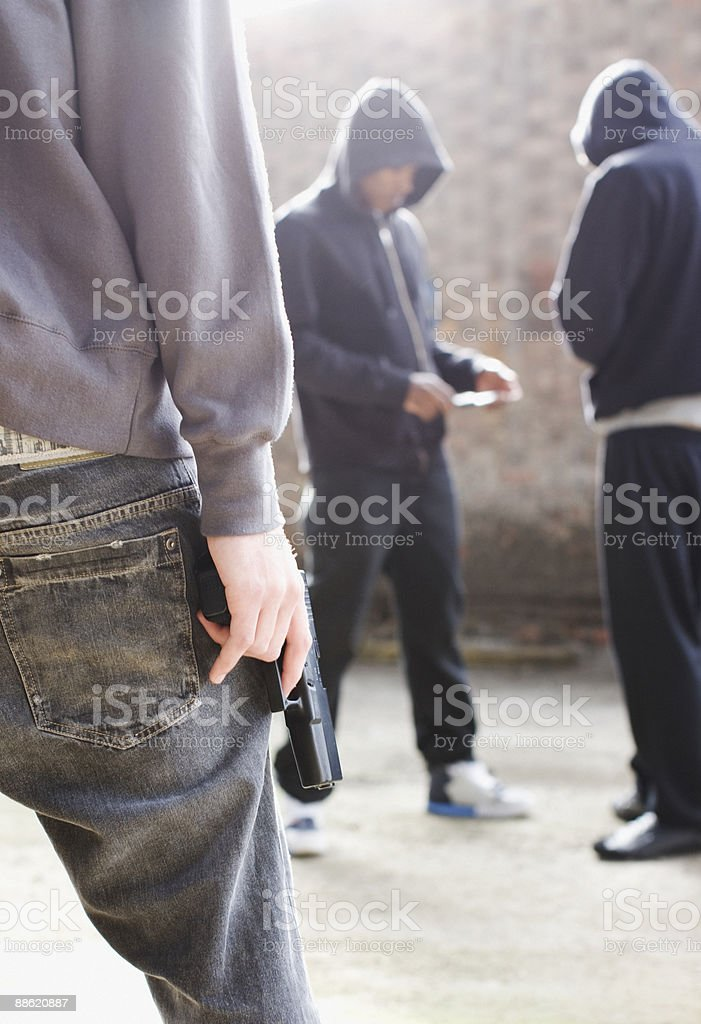Man with gun approaching drug dealers stock photo