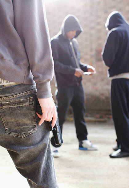 Man with gun approaching drug dealers  drug dealer stock pictures, royalty-free photos & images