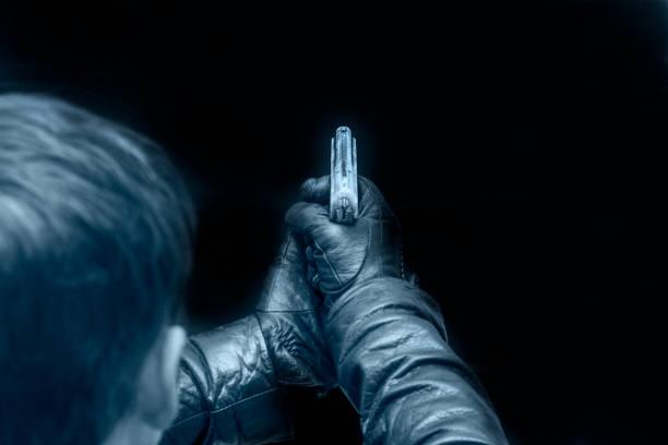 mann mit gewehr in der hand vor einem dunklen hintergrund - killer workouts stock-fotos und bilder