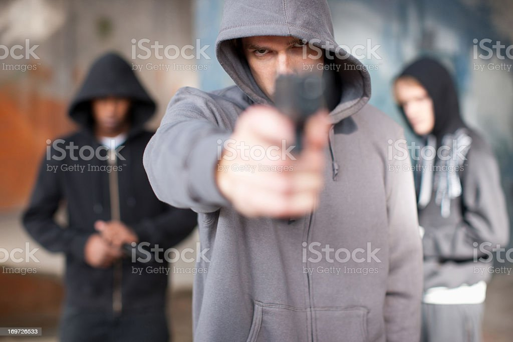 Man with gun pointed at viewer stock photo
