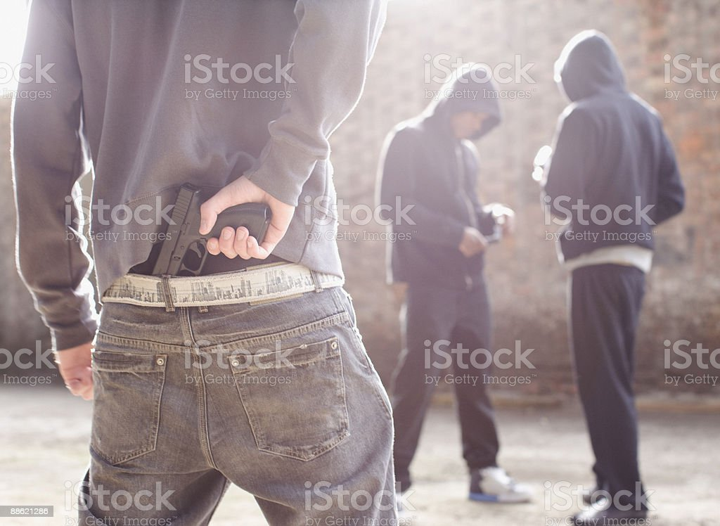 Man with gun robbing drug dealers stock photo