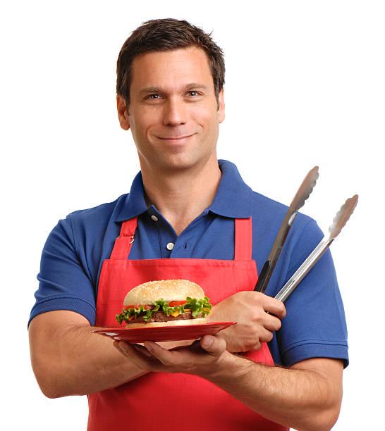mann mit hamburger und barbecue greifzange, isoliert auf weißem hintergrund - grillschürze stock-fotos und bilder