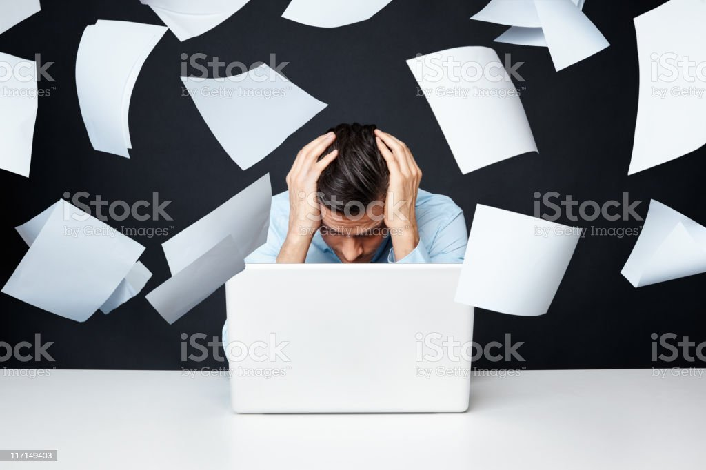 Man with hand on head looking at laptop with papers flying stock photo
