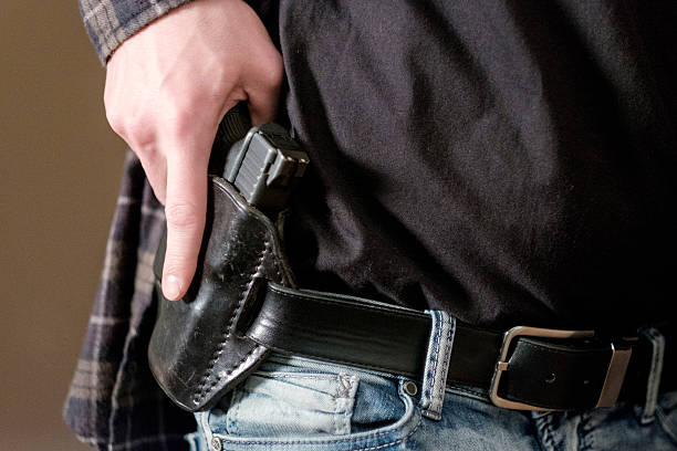 Man with Handgun in Holster A man drawing a gun from a leather holster on his belt. self defense stock pictures, royalty-free photos & images
